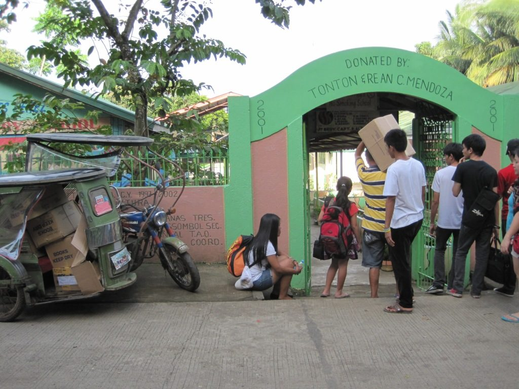The Bibles arrive via tri-cycle at the school.