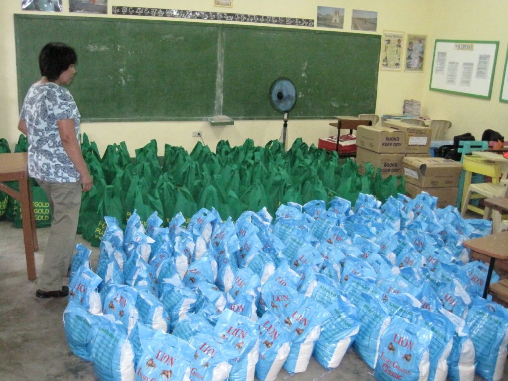 Lilia makes final counts on rice and food for distribution.
