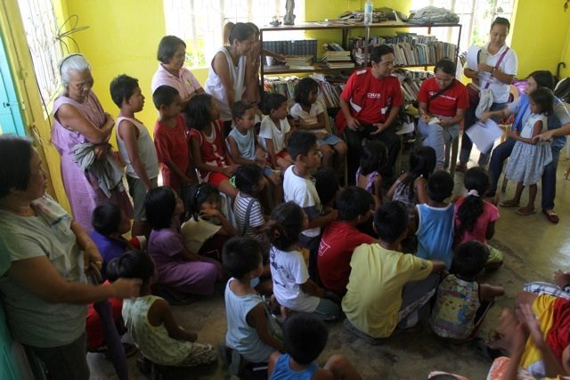 Lilet Sarabia (far right) conducts an impromptu stress-debriefing with children at an elementary school in Panaytayon, where the NDR team had facilitated a WASH assessment