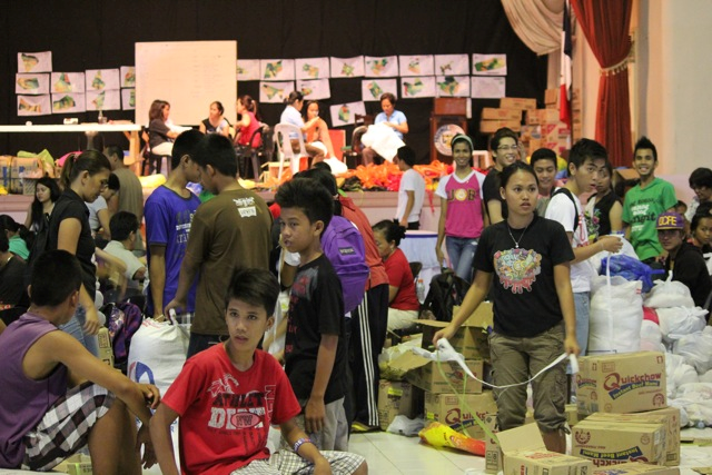 Bohol Island State University students assist with the re-packaging of food relief