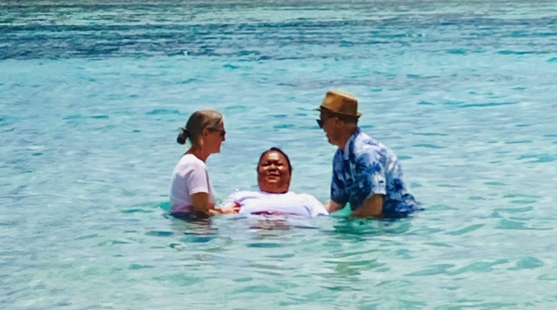 2 people baptizing an adult female