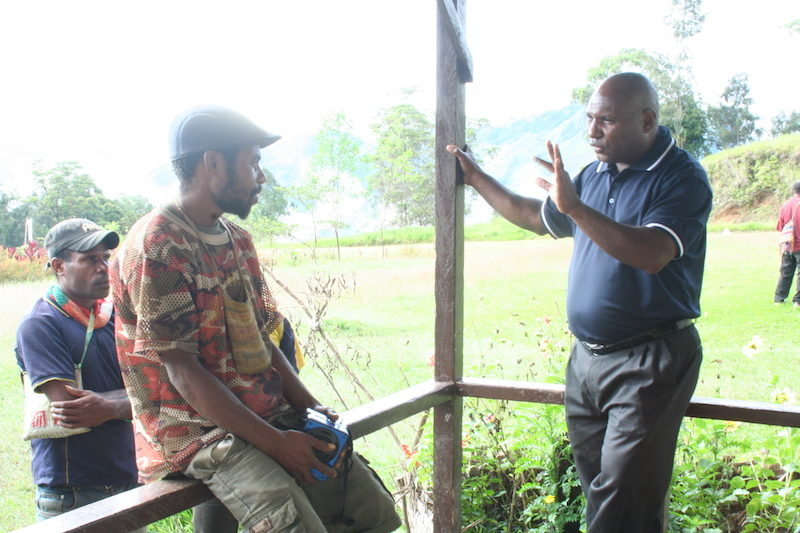 Rev. Daniel Eka speaks with man who listens to radio programs on portable radio.