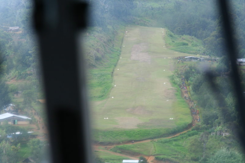Landing at the remote Dusin airstrip which actually runs up a mountain, as seen from the cockpit of the MAF plane.